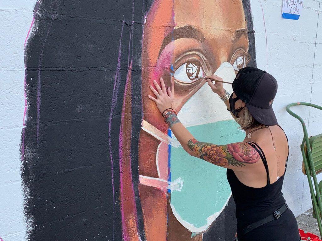 Artist Lindsay McGlynn Paints Healthcare Mural On Lake Worth Beach Florida Unity Wall